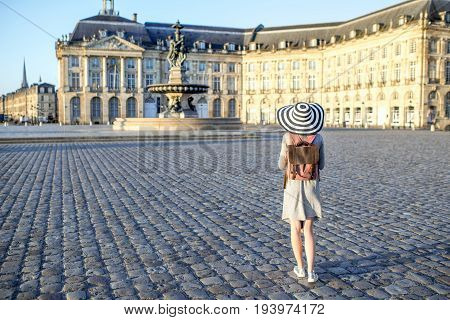Young woman tourist standing back enjoying view on the famous Bourse square with beautiful buildings and fountain in Bordeaux city during the morning