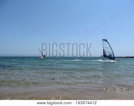 Two windsurfers with a blue and red sail in the sea. Water entertainment for sports people at sea or in the ocean
