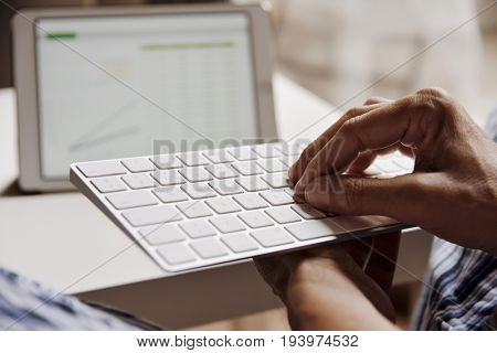 closeup of a young caucasian man in pajamas typing in a computer keyboard