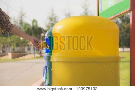blue and yellow plastic trashcan in the park at summer. Colored trash containers.