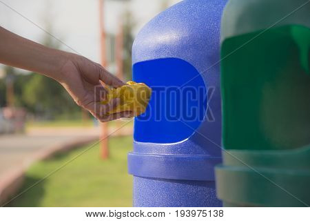 Female hand throwing crumpled yellow plastic into blue plastic trashcan.