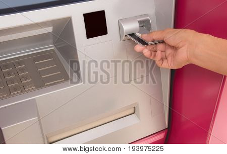 Hand of a woman with a credit card using an ATM. Woman using an ATM machine. Woman using her credit card on ATM.