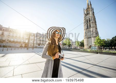Young woman tourist walking with photocamera on the Pey-Berland square with bell tower on the background during the morning in Bordeaux city
