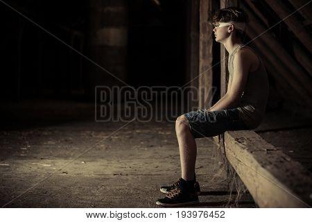 Blindfolded Boy Sitting In A Darkened Attic