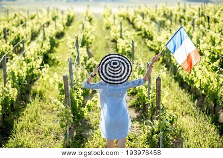 Young woman in striped hat with french flag enjoying beautiful sunset view on the vineyard in Bordeaux region in France