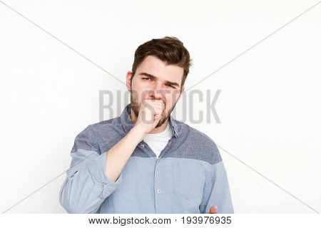 Portrait of yawning man. Sleepy guy gape and close his mouth with hand, isolated on white background