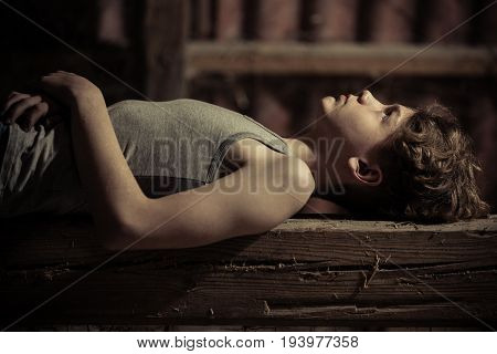 Close Up Side View Of Boy Laying On Wooden Bench