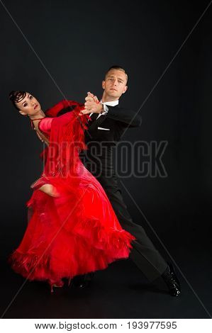 dance ballroom couple in a dance pose on black background. sensual professional dancers dancing walz tango slowfox and quickstep.