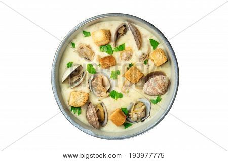 An overhead photo of a bowl of clam chowder, decorated with fresh parsley and croutons, isolated on a white background
