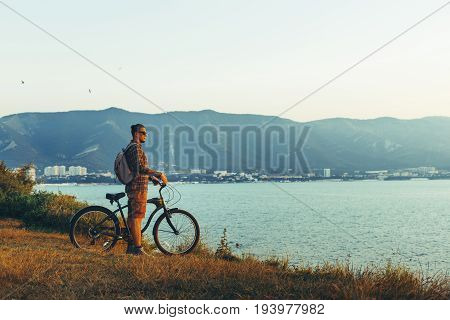 Young Guy Standing With Bike On Coast And Enjoying View of Nature Sunset Vacation Traveling Relaxation Resting Concept