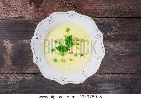An overhead photo of vichyssoise, French potato and leeks soup, with chopped green onions, pink peppercorns, and mint leaves, on dark rustic texture with a place for text