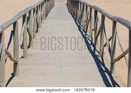 wooden footbridge on sand beach coast line