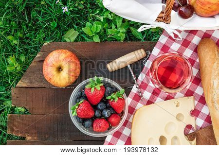 Overhead photo of picnic with apples, glass of rose wine, fresh fruit in plastic container, a piece of Dutch cheese, and a baguette, on a rustic wooden board on top of green grass, with place for text