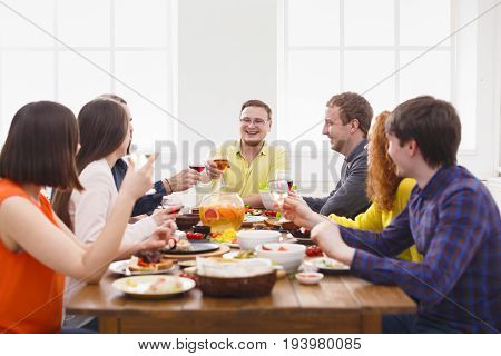 Happy friends clink glasses, saying cheers at party dinner table in cafe, restaurant or at home. Young people company celebrate indoors.