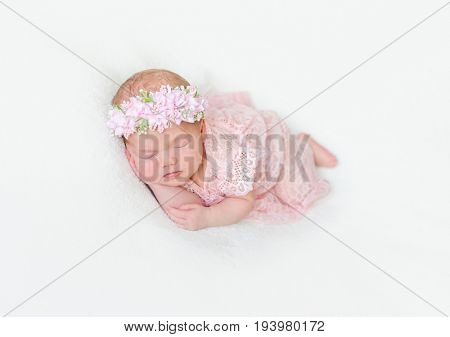 infant dressed in pink laced costume napping tightly