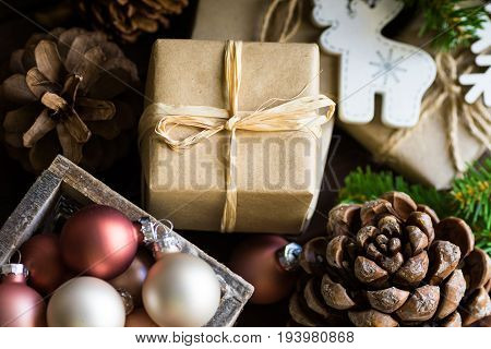 Christmas and New Year gift boxes wrapped in craft paper twine bow pine cones fir tree branches ornaments baubles in wood box cozy festive atmosphere top view