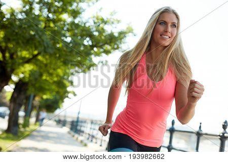 Beautiful young blonde woman running outdoors.