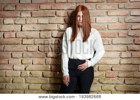 Serious young ginger woman standing against brick wall.
