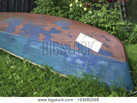Capsized wooden boat with attached blank paper sheet for further design, outdoor cropped photo