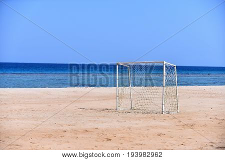 Goalpost on beach for playing football for summer sport on background of blue sea and sky copy space