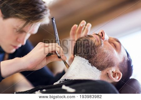 grooming and people concept - man and barber hands with straight razor shaving beard at barbershop poster