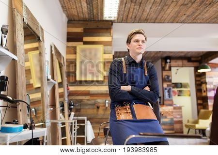 profession, grooming and people concept - male stylist or hairdresser with scissors in apron at hair salon or barbershop