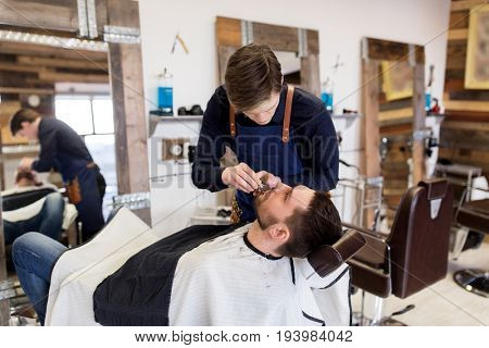 grooming and people concept - man and barber with trimmer or shaver cutting beard at barbershop