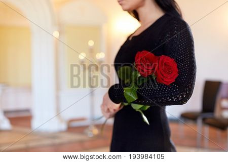 people and mourning concept - woman with red roses at funeral in church