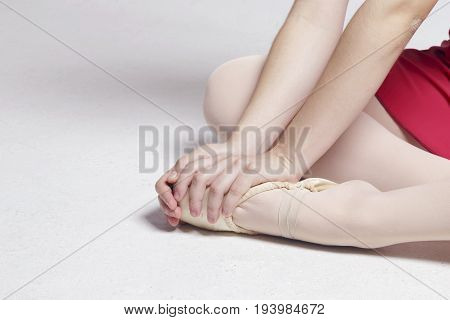 Ballerina Sitting On A White Floor, Touching Her Foot.