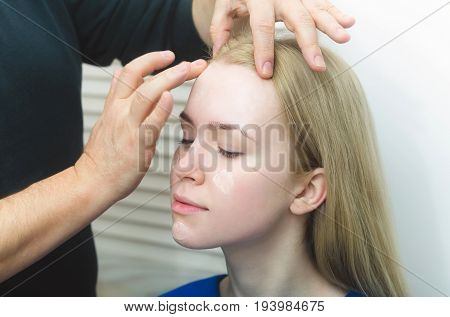 Visagiste hands applying concealer on woman face skin with closed eyes. Cute girl or fashionable model with long blond hair in beauty salon. Visage makeup cosmetics and skincare
