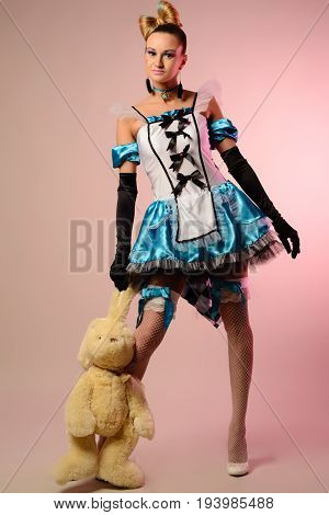 Young Woman Dressed As Alice In Wonderland, With A Rabbit In The Hands