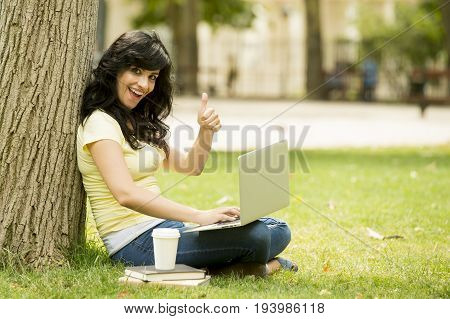 Attractive Beautiful Latin Woman Happy Working On Her Laptop Outside In A Green Park
