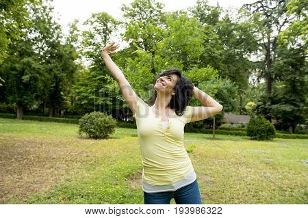 Happy Attractive Latin Woman Throwing Her Hands In The Air Relaxing