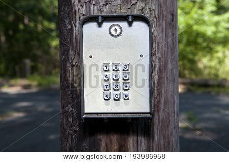 An outdoor electronic keypad on a post