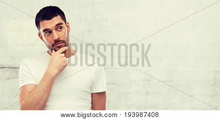 doubt, expression and people concept - man thinking over gray wall background