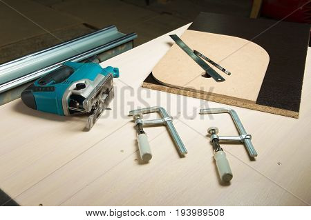 Prepared tool jigsaw with wood clamps and a pencil with a ruler lying on the carpenter's desk