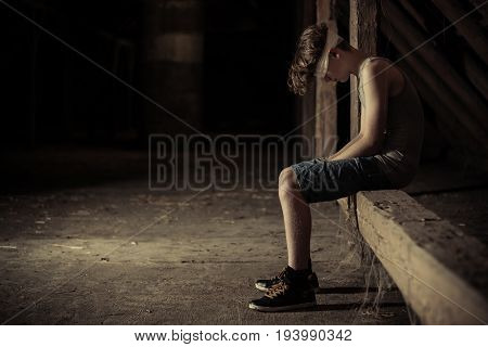 Sad child sitting on wooden plank outside for concept about abuse neglect or depression with copy space