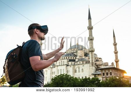 A traveler with virtual reality glasses. The concept of virtual travel around the world. In the background, the blue mosque Sultanahmet in Istanbul. Modern imaging technology.