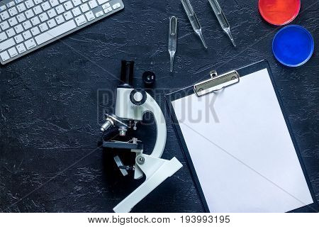 Workplace of doctor. Microscope, ampoule, Petri dish, pad on grey stone background top view.