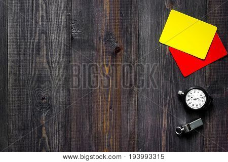 Yellow and red referee cards, stopwatch and whistle on wooden background top view.