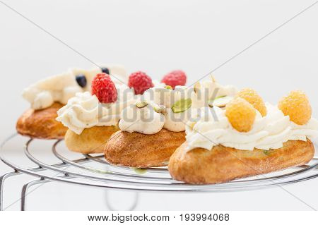 Eclairs With Vanilla Cream On White Background