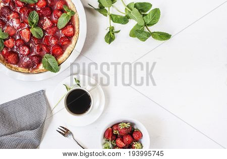 Strawberry pie on white background next to a cup of coffee fork muffin towel
