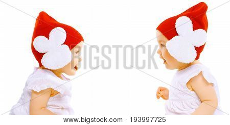 Closeup Portrait Two Baby Twins In Red Hats Sitting Face To Face On A White Background