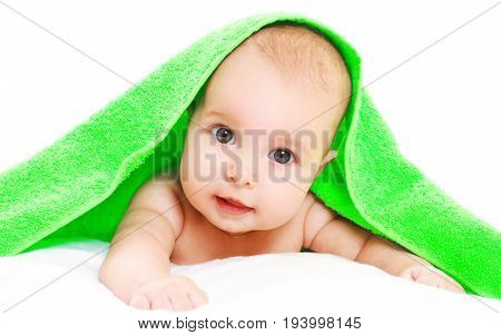 Portrait Close-up Of Face Cute Baby Under Green Towel On A White Background