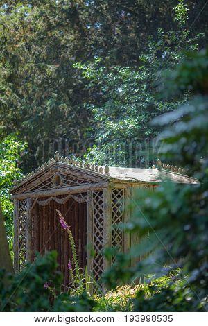 Secret summer house. Ornamental wooden trellis garden gazebo seating area. Beautiful garden retreat.