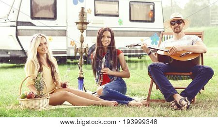 Happy, smiling hippie friends having a picnic outdoors at summer.