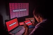 Young Asian male frustrated confused and headache by ransomware attack on desktop screen notebook and smartphone cyber attack and internet security concepts poster