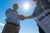 Builders Handshake, Architect And Contractor Agreement During Meeting Discussing Blueprint Buiding Plan poster