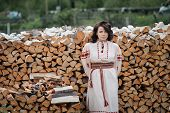 Portrait of a beautiful girl in Slavic clothes on the background of a woodpile. Summertime poster