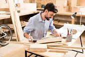 Jolly young lumber craftsman with beard sitting at desk and measuring planks by long aluminium ruler. He is using graphite pencils and whatman paper in his job poster